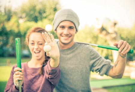 Schöne Paare, die im Golfclub Standard-Bild