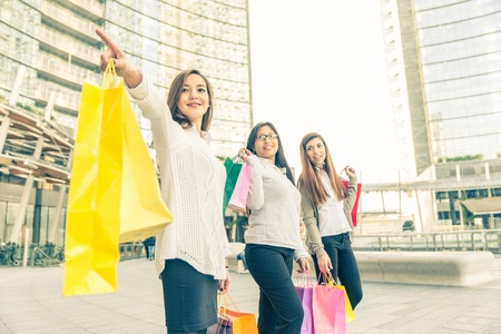 Women with shopping bags - Portrait of three pretty girls walking and looking at shops photo