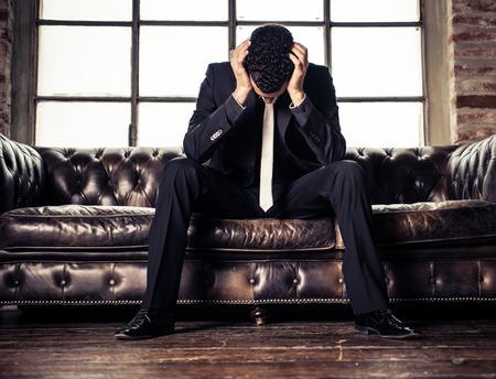 persona deprimida: Hombre de negocios deprimido sentado en el sofá - Imagen negativa de la persona joven triste