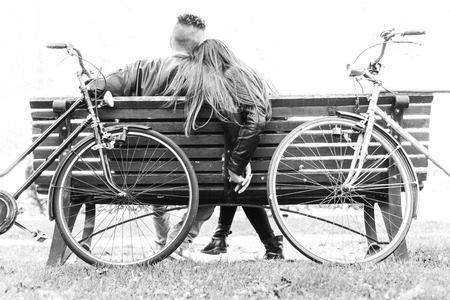 bicycle girl: Couple on a bench - Two lovers sitting on a bench in a park and holding themselves by hands - Concepts of autumn,love,togetherness,relationship