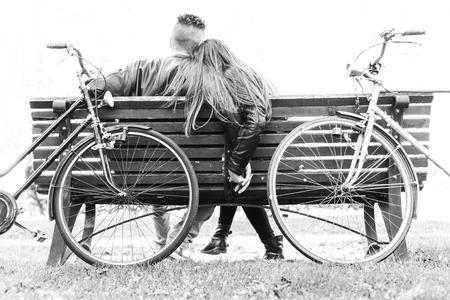 banc de parc: Couple sur un banc - Deux amants assis sur un banc dans un parc et se tenant par les mains - Concepts de l'automne, Amour, Ensemble, relation