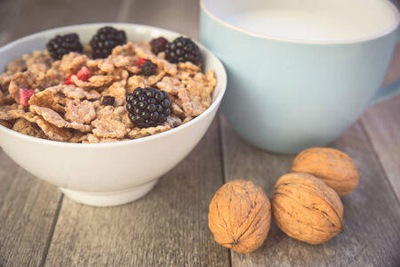 natual: Milk and muesli with berries - Healthy breakfast with fresh natual igredients - Close up on breakfast table