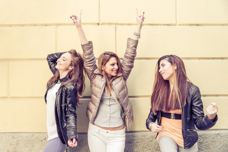 singing: Group of attractive young women  having fun outdoors - Three playful girls singing and dancing - Fashion models posing