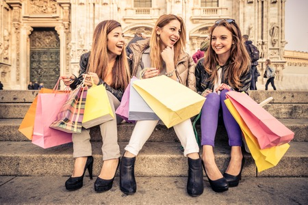 gift bags: Women with shopping bags - Portrait of three pretty girls sitting on a staircase while laughing and talking Stock Photo