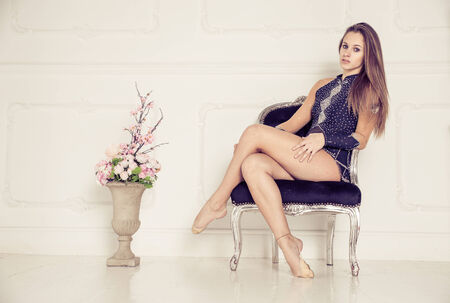 Fashion model with gymnast outfit - Pretty young caucasian woman with long hair crossing her legs - Stock Photo