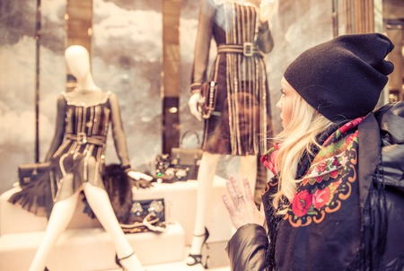 Pretty woman looking at window shop - Sale in clothes shop