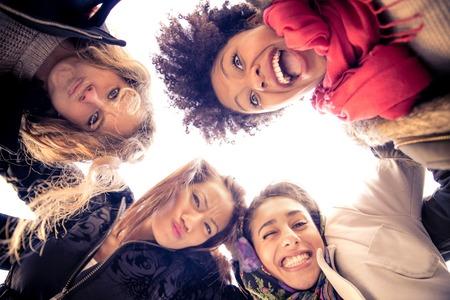 Groep van aantrekkelijke jonge vrouwen van verschillende etnische knuffelen in een cirkel - Vier studenten lachend naar de camera - de beste vrienden die samen tijd doorbrengen Stockfoto