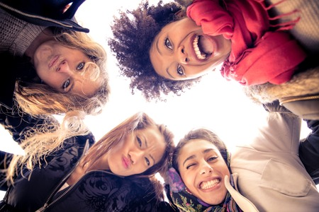 Gruppe von attraktiven jungen Frauen der verschiedenen Ethnien umarmt in einem Kreis - Vier Studenten Lächeln in die Kamera - Best friends Zeit miteinander zu verbringen