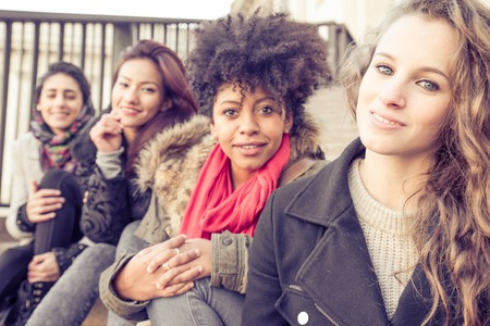muslim girl: Group of attractive young women of different ethnies sitting on stairs and smiling at camera - Four students sitting outside university - Best friends spending time together Stock Photo