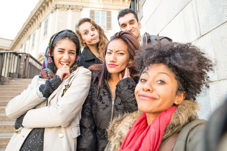 Group of attractive young women of different ethnics taking a selfie - Students having fun - Best friends spending time together - Tourists photographing on a city tour Standard-Bild