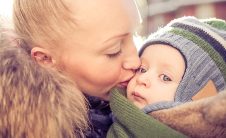 Mom kissing her handsome son - Woman and baby outdoors photo
