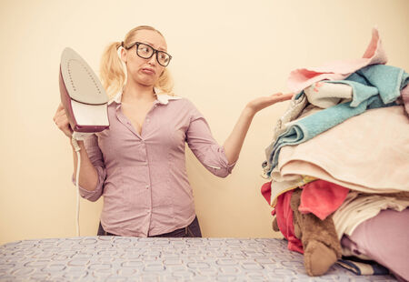 Housewife with iron looking unhappy at a pile of clothes photo