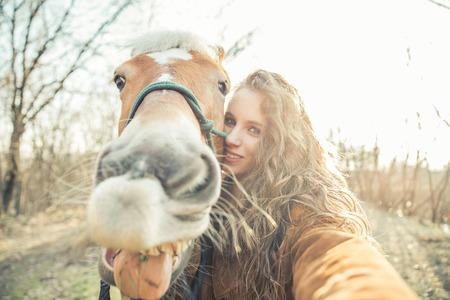 陽気な馬と面白い selfie を取っているかなり若い女の子
