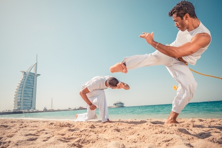 arts: Capoeira team training on the beach - Martial arts athletes fighting
