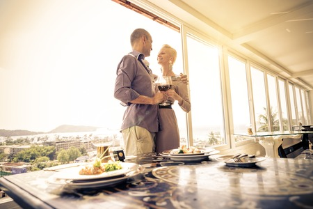 Beautiful happy couple having romantic dinner at sunset in a luxury restaurant - Woman and her husband celebrating wedding anniversary