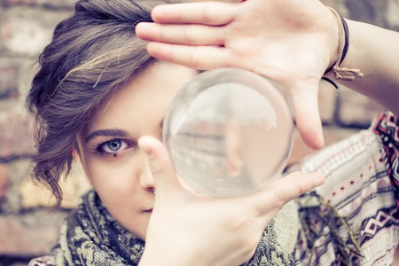 Portrait of young beautiful girl with blue eyes balancing a crystal ball on the hand - Woman performing contact juggling