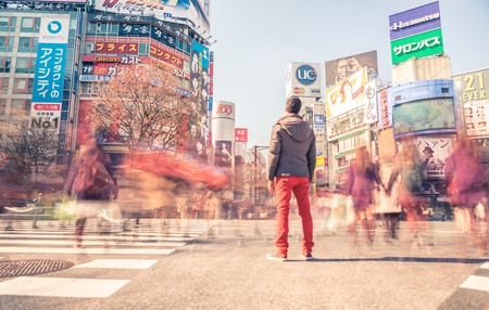 scramble: TOKYO,JAPAN - FEBRUARY 11,2015: Man standing in Shibuya square. The scramble crosswalk is one of the largest in the world.