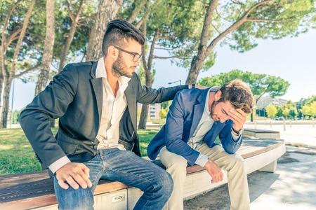 남자가 자신의 재정 문제에 대한 절망 그의 친구를 지원 - 우울 사람을 지원하는 젊은 비즈니스 남자 - 스톡 콘텐츠
