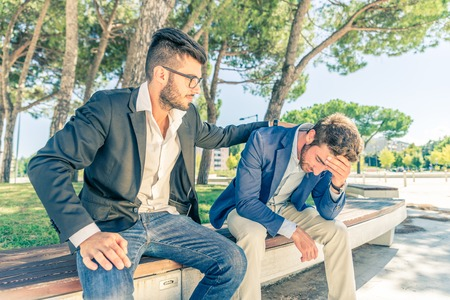 economic depression: Young business man supporting a depressed person - Man supporting his friend despairing for his financial problems - Stock Photo