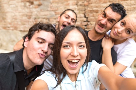 boy friend: Group of friends taking a selfie - Tourists taking a photograph on a day trip Stock Photo