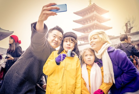 asakusa: Happy multiethnic family taking a picture in front of Sensoji Temple in Tokyo. Stock Photo