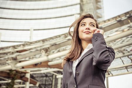 mujer trabajadora: Mujer de negocios que habla en el tel�fono - mujer asi�tica con elegante traje y rascacielos en el fondo - de negocios, tecnolog�a, conceptos multirraciales