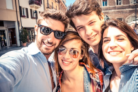 friends hugging: Group of friends taking a selfie - Students smiling at camera and having fun outdoors in a sunny day - Students enjoying the coming of spring