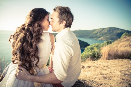 Paar in liefde het kussen bij zonsondergang - Liefhebbers op een romantische date buiten Stockfoto