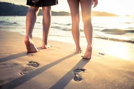 Couple of lovers walking on the each at sunset - Foot prints on the beach 免版税图像 - 37668788