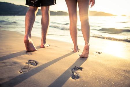 luna de miel: Pareja de amantes que caminan por la cada al atardecer - Impresiones del pie en la playa
