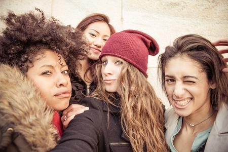 women friends: Group of attractive young women of different ethnics taking a selfie - Four students smiling at camera - Best friends spending time together Stock Photo