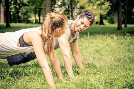 woman hard working: Young couple doing push ups in a park - Two athletes training outdoors Stock Photo