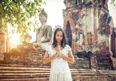 寺院で祈りのタイの女性