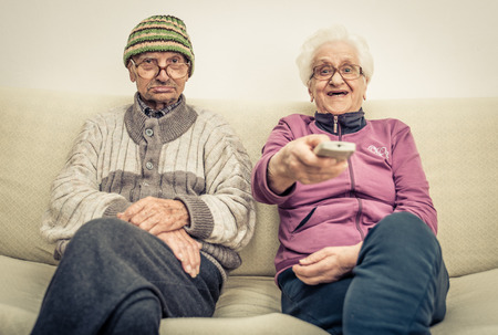 happy senior couple: old couple watching tv