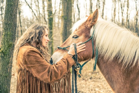 stroking: Beautiful woman stroking a brown horse - Pretty caucasian model woth stallion outdoors Stock Photo