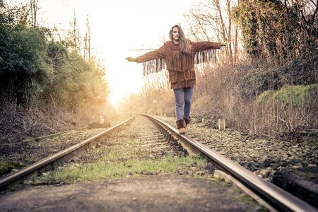adrenaline: One young woman balancing on rail - Pretty girl walking on rail in search for adrenaline
