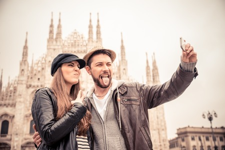 self   portrait: Happy tourists taking a self portrait with phone in front of Duomo cathedral,Milan - Couple travelling in Italy