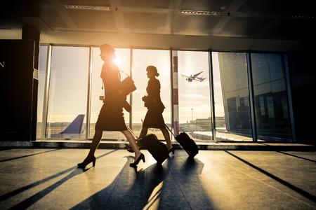 Silhueta dos turistas em airpor transportando luggage- viajantes que esperam o vôo no aeroporto
