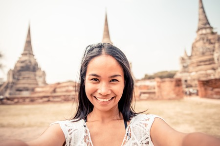 Asian woman taking a selfie at temple in Ayutthaya, Thailand - Tourist recording while sightseeing in Asia