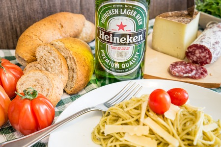 international beer: MILAN,ITALY - MARCH 27, 2015: bottle of Heineken  beer on a table with some food. Heineken Lager Beer is produced by the Dutch brewing company Heineken International and exported all over the world