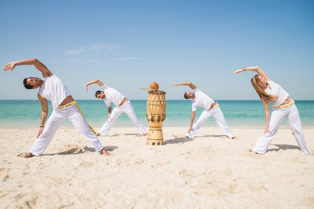 Group of people doing stretching - Capoeira team training on the beach - Martial arts athletes performing stunts