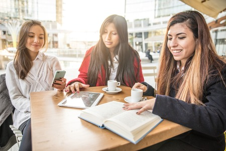 youth culture: Group of friends at restaurant drinking coffee - Women with books,tablets and smart phone - Concepts about technology,communication and youth culture Stock Photo