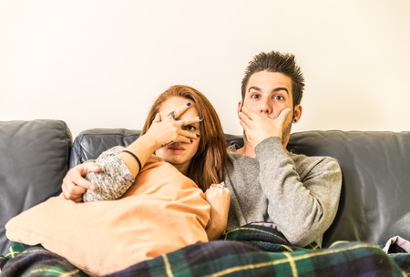 Couple watching horror movie on television on the couch - family,recreation,leisure,togetherness concept