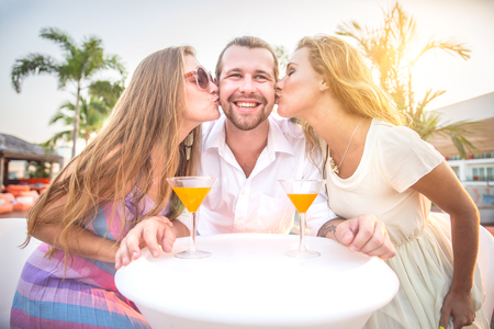 hot drink: Two beautiful women kissing on cheeks a man - Friends at party drinking cocktails and having fun - Three tourists drinking aperitif in a tropical luxurious restaurant Stock Photo
