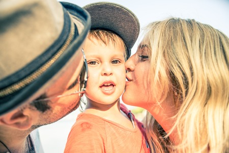 beach kiss: Mom and dad kissing their handsome son - Family and baby outdoors