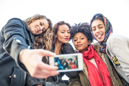ethnics: Group of attractive young women of different ethnics taking a selfie - Students having fun - Best friends spending time together - Tourists photographing on a city tour Stock Photo