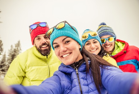 skis: Group of friends taking a selfie - Four snowboarders taking a self portrait with mobile phone - Tourists having fun while skiing - Concepts about winter,christmas,winter vacation and skiing