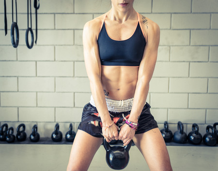 gym: woman training with kettlebells Stock Photo