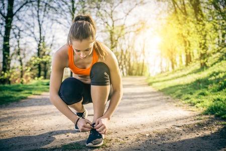 mujeres fitness: Mujer juguetona joven que consigue listo para empezar a correr entrenamiento - Atleta corriendo al aire libre al atardecer - Atractiva chica haciendo deporte para perder peso y mantenerse en forma