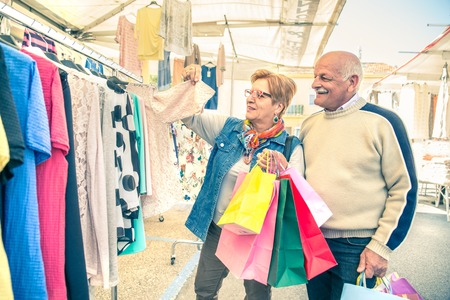 Mature woman looking clothes at market - Senior couple with shopping bags walking and buying some dresses to renew wardrobe photo